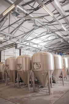 Foto vertical de tanques de cerveja na fábrica de produção da microcervejaria