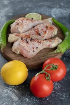Foto vertical de tomate orgânico fresco e limão com pernas de frango cru.