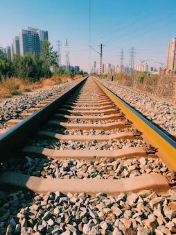 Foto vertical de trilhos de ferrovia com edifícios
