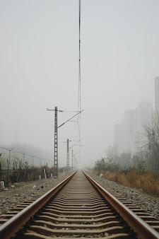 Foto vertical de trilhos de trem sob um céu nublado