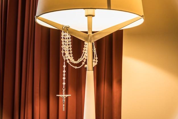 Foto vertical de um abajur de cabeceira e uma cruz de prata pendurada e brilhando sob a luz do abajur