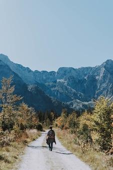 Foto vertical de um alpinista se aventurando por uma estrada de cascalho estreita em direção a montanhas rochosas