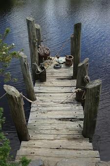 Foto vertical de um antigo deck em um lago sob a luz do sol