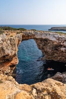 Foto vertical de um arco de pedra sobre a água em maiorca, espanha