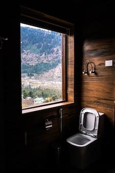 Foto vertical de um assento de vaso sanitário perto da janela com a bela vista de uma paisagem