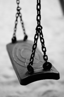 Foto vertical de um balanço preso a correntes de metal