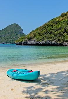 Foto vertical de um barco a remo azul na praia, perto do belo oceano e das montanhas