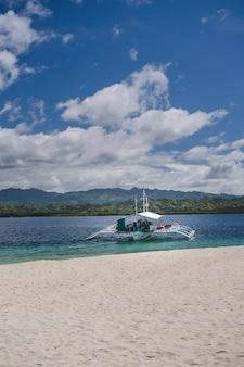 Foto vertical de um barco branco na praia atrás das montanhas