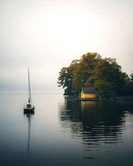 Foto vertical de um barco e uma pequena casa com árvores altas na costa do oceano