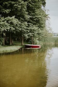 Foto vertical de um barco em um lago cercado por árvores