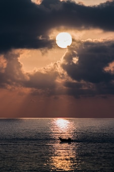 Foto vertical de um barco em um mar ao pôr do sol