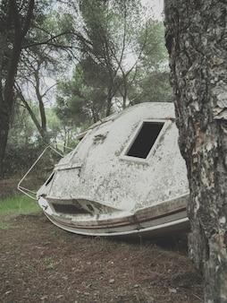 Foto vertical de um barco enferrujado abandonado em uma floresta durante o dia