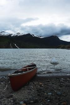 Foto vertical de um barco na margem do lago no inverno