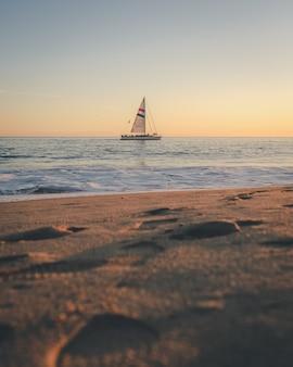 Foto vertical de um barco no mar à distância