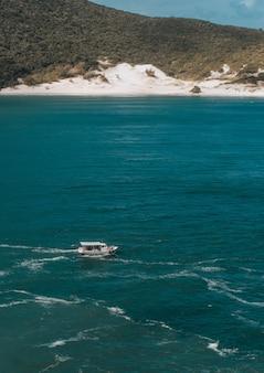 Foto vertical de um barco no mar com uma colina