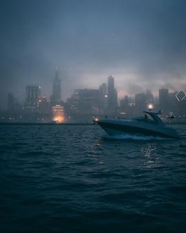 Foto vertical de um barco no oceano com as silhuetas de edifícios altos