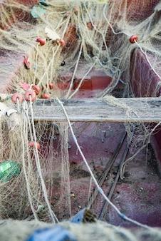 Foto vertical de um barco velho coberto por uma rede de pesca