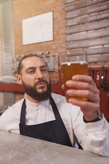 Foto vertical de um bartender profissional examinando cerveja light no copo
