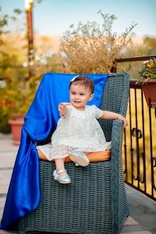 Foto vertical de um bebê adorável e lindo sentado em uma cadeira de palha no verão