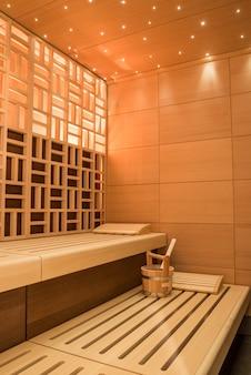 Foto vertical de um belo design de sala de sauna com azulejos de parede e banco de madeira