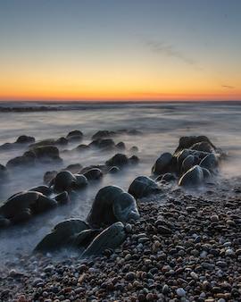 Foto vertical de um belo pôr do sol em uma praia rochosa