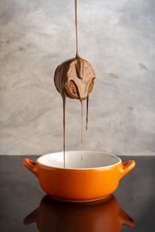 Foto vertical de um biscoito saboroso sendo coberto por chocolate em uma tigela de laranja