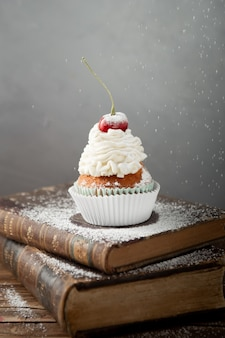 Foto vertical de um bolinho delicioso com creme e cereja no topo dos livros
