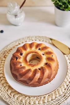Foto vertical de um bolo de anel em uma mesa branca
