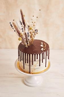 Foto vertical de um bolo de baunilha com gotas de chocolate e flores no topo