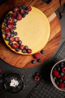 Foto vertical de um bolo de queijo com frutas vermelhas em cima de uma placa de madeira com frutas vermelhas na lateral
