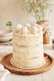Foto vertical de um bolo raffaello em uma bandeja de madeira com uma toalha de mesa branca por baixo