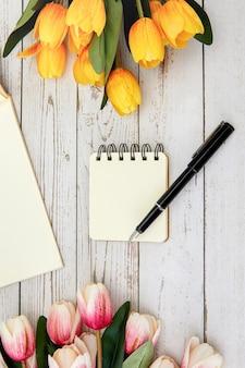 Foto vertical de um caderno em branco e uma caneta, algumas flores em uma superfície de madeira