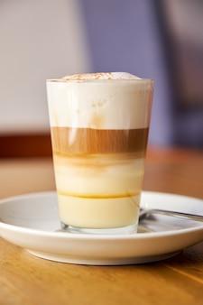 Foto vertical de um café com leite servido em um copo de cristal em cima de um prato de porcelana sobre uma superfície de madeira