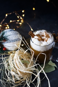 Foto vertical de um café de natal com canela e espuma, ao lado de enfeites de natal