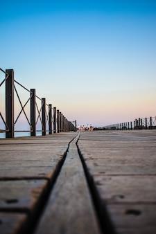 Foto vertical de um cais de madeira cercado por cercas sob o céu azul ao anoitecer