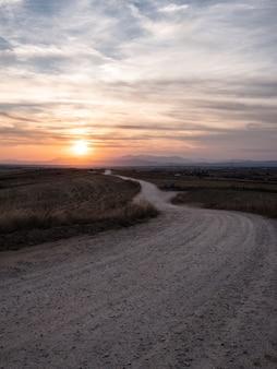 Foto vertical de um caminho em um campo gramado com uma vista deslumbrante do pôr do sol no