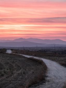 Foto vertical de um caminho em um campo gramado com uma vista deslumbrante do pôr do sol