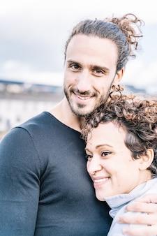 Foto vertical de um casal abraçado pelo ombro com o mar fora de foco