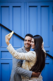 Foto vertical de um casal caucasiano fazendo uma selfie