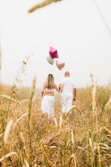 Foto vertical de um casal caucasiano segurando balões em forma de coração no campo