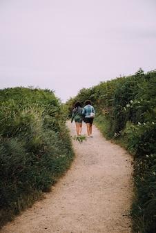 Foto vertical de um casal de lésbicas caminhando em um caminho cercado por vegetação