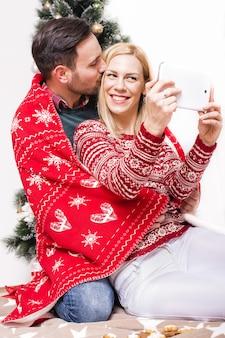 Foto vertical de um casal feliz com um cobertor vermelho tirando uma selfie com uma árvore de natal