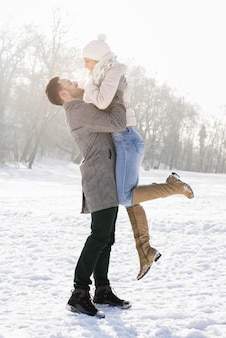 Foto vertical de um casal feliz curtindo a bela neve em um dia frio de inverno
