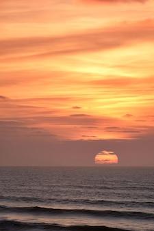 Foto vertical de um cenário de pôr do sol de tirar o fôlego sobre o oceano
