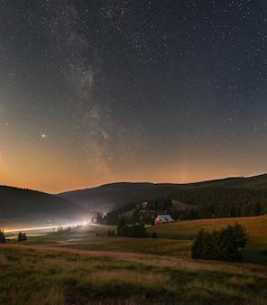 Foto vertical de um céu noturno estrelado com a via láctea sobre as montanhas gigantes
