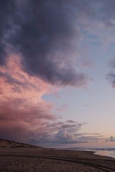Foto vertical de um céu roxo de tirar o fôlego na praia após o pôr do sol
