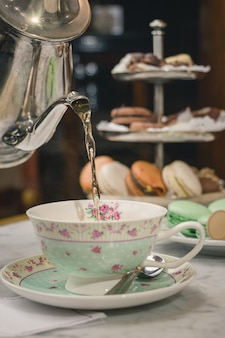 Foto vertical de um chá servindo em uma xícara sobre uma mesa de mármore com sobremesas