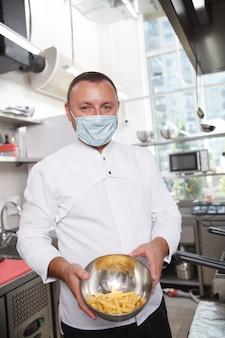 Foto vertical de um chef profissional usando msk facial de médico, segurando uma tigela com batatas fritas