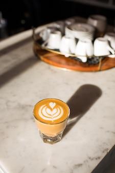 Foto vertical de um copo de café com leite na mesa sob as luzes