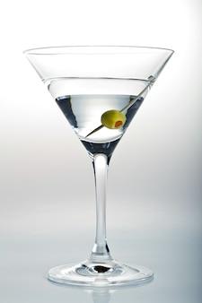 Foto vertical de um copo de martini e uma azeitona em branco